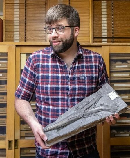 Photograph of Robert holding an ichthyosaur fossil